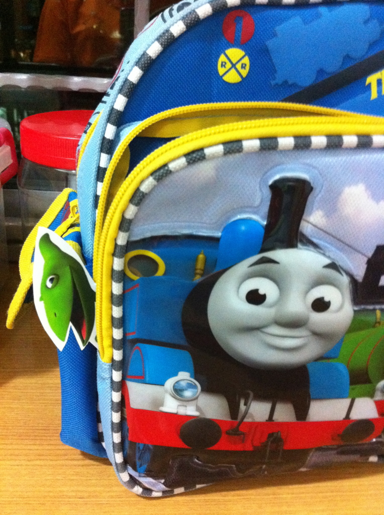 don pteranadon peeking out from thomas the train bag